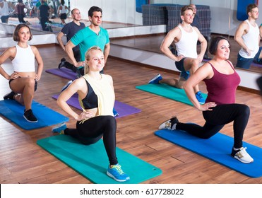 Young positive people exercising in dance hall