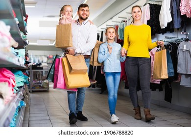 Young positive smiling parents with two little girls shopping in mall, carrying purchases