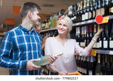 young positive spouse buys wine in the store