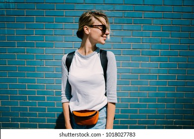 Young positive tourist woman dressed in street style wear looking away standing on blue wall background,smiling hipster girl in trendy casual clothing enjoying leisure outdoors posing at urban setting