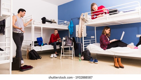 Young positive travelers communicating while resting in hostel dormitory