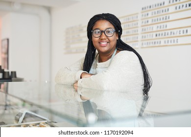 Young positive waitress leaning by display with pastry while looking at you in cafeteria