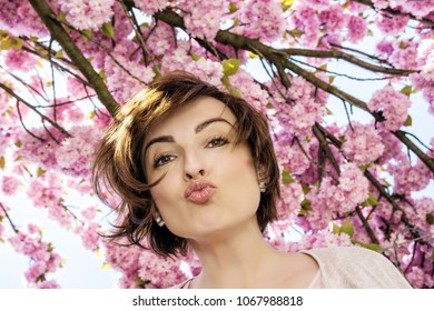 Young positive woman with cherry lips posing under sakura flowers. Beauty and nature.