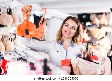 Young positive woman choosing pretty clothing in lingerie shop