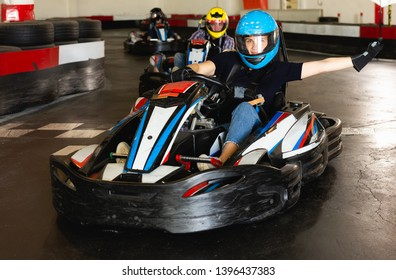 Young positive woman with friends driving cars for karting in sport club