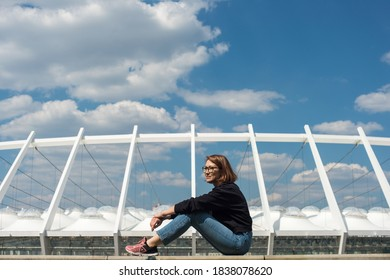 Young positive woman in glasses sitting on a barrier fence against blue sky and a sport stadium