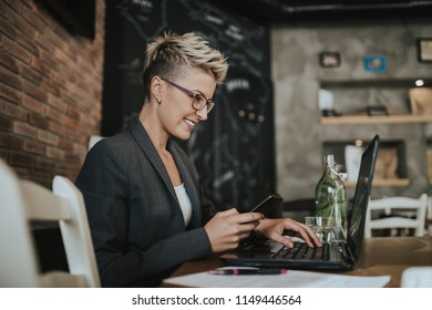 Young positive woman with glasses working in modern office.