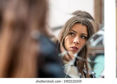 eine junge, positive Frau betrachtet ihr Spiegelbild