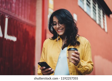 Young positive woman in optical eyeglasses smiling while typing an sms message on smartphone device, attractive hispanic student girl listening to music and reading new on cellphone outdoors