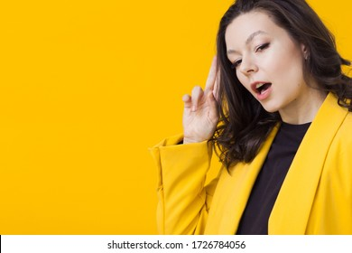 Young positive woman in yellow, bright portrait on a yellow background.