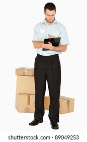 Young post employee with parcels taking notes on his clipboard against a white background