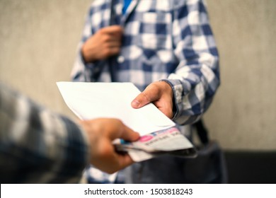 young postman deliver the newspaper envelope and documents at home