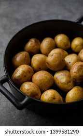 Young potatoes in iron pot