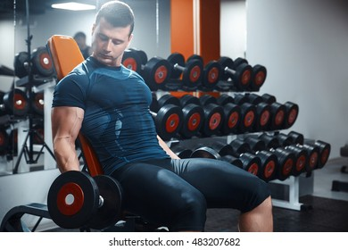 Young power athletic man doing exercise on biceps with heavy dumbbells sitting on bench in gym.