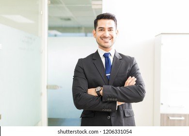 Young and powerful Hispanic lawyer standing arms crossed in office
