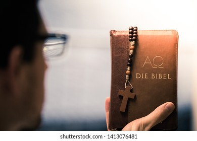 "Young preacher is holding the holy bible, praying, ""Die Bibel"""