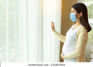 Young pregnant asian woman in medical mask stay alone at home for self quarantine. home quarantine, prevention covid 19, coronavirus outbreak situation concept Pregnancy mother looking through window