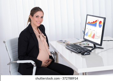 Young Pregnant Businesswoman Sitting At Desk In Office