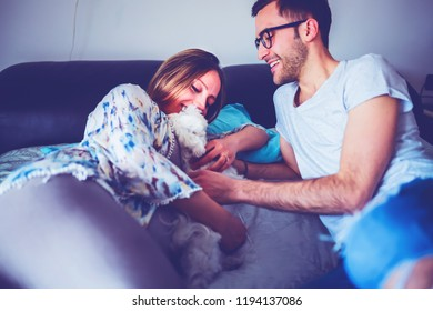 young pregnant coupke indoors bedroom having fun with puppy dog - family life, new beginning, life event concept