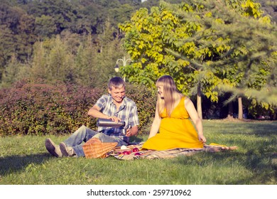 young pregnant couple relaxing on a picnic in the park
