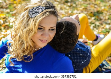 young pregnant couple sitting on yellow leaves in the park in autumn