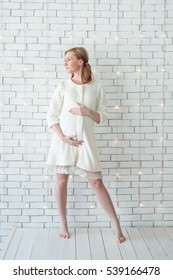 Young pregnant girl smiling and standing near white wall