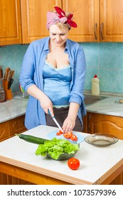 young pregnant housewife cuts tomatos on a kitchen