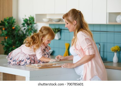 Young pregnant mother with daughter making apple tart together grandmother check recipe
