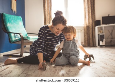 young pregnant mother with dreadlocks, and her son play and reading a book on sofa, lifestyle, real interior toning