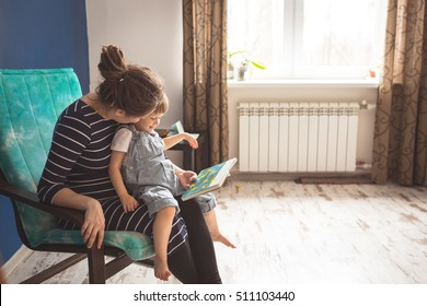 young pregnant mother with dreadlocks, and her son play and reading a book on sofa, lifestyle, Real interior, toning, selective focus