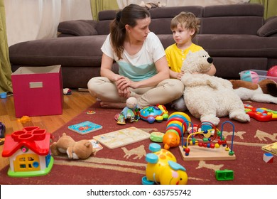 Young pregnant mother and her little son, at home. Mother and little son  sit on a floor. Mom tired to tidy up the house. Child scattered toys. Mess in the house
