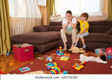 Young pregnant mother and her little son, at home. Mother and little son  sitting on the couch. Mom tired to tidy up the house. Child scattered toys. Mess in the house