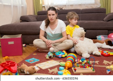 Young pregnant mother and her little son, at home. Mother and little son  sit on a floor. Mom tired to tidy up the house. Child scattered toys. Mess in the house. Mother has quarreled with the son.