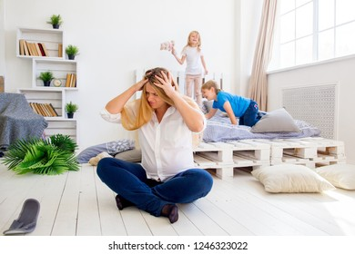 Young pregnant mother is tired because her kids play