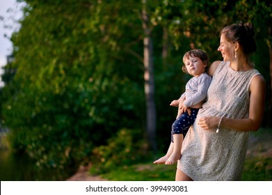 Young pregnant mother walking with her little son in summer park near the lake