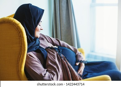 Young pregnant muslim arabic woman sitting in armchair at home