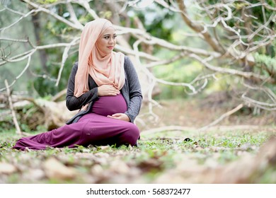 Young pregnant Muslim woman sitting down with hands on her belly