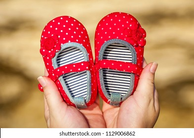 Young pregnant woman about to become mother holding tiny red baby girl shoes. Expecting a girl daughter concept image. Expecting mother, future parent.