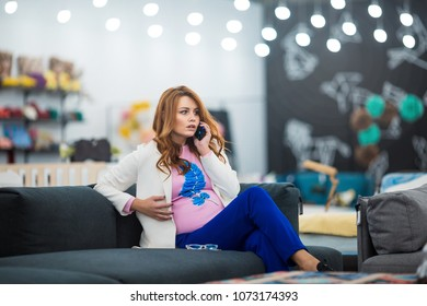Young pregnant woman calling with cell telephone while sitting alone in furniture store, attractive female having talking conversation with mobile phone while rest on sofa.