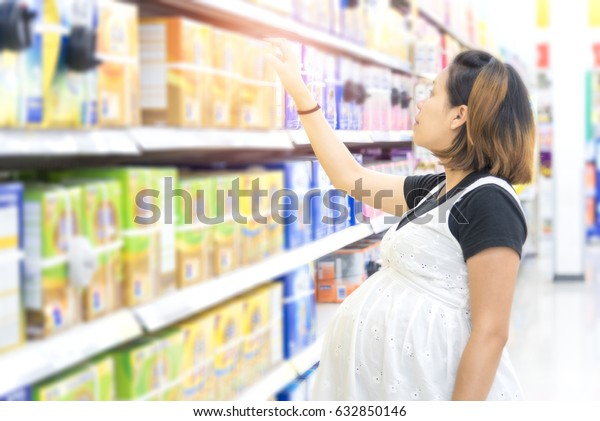 Young pregnant woman choosing milk powder at shopping in dairy supermarket store