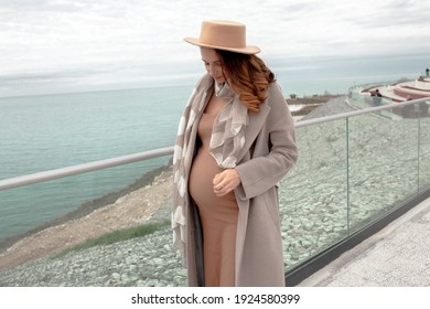 Young pregnant woman dressed coat, dress ans hat walking outdoor in the street. Lifestyle concept