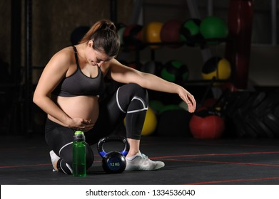 Young pregnant woman drinking wate from plastic bottle after workout in the gym