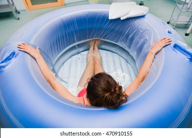Young pregnant woman during labour in hospital sitting in a water pool.