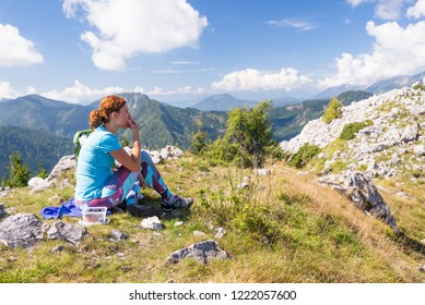 Young pregnant woman is eating food while sitting on the meadow in the mountains. Active pregnancy and healthy living concept.