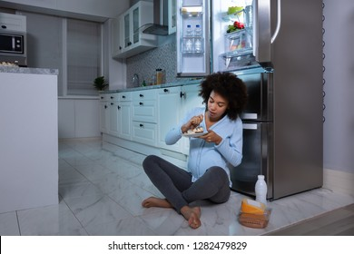 Young Pregnant Woman Eating Piece Of Cake Sitting In Front Of Open Refrigerator At Kitchen
