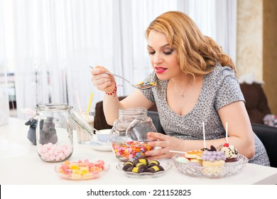 Young pregnant woman eating sweets with a spoon, sitting at the kitchen table full of sweets