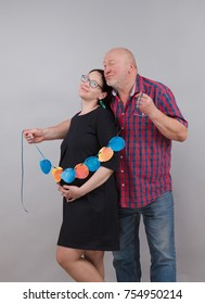 Young pregnant woman and elderly grandfather posing on gray background