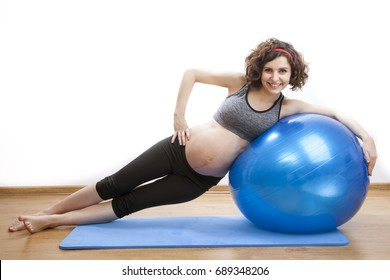 Young pregnant woman exercises