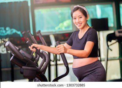 Young pregnant woman in fitness clothes exercising exercising on the elliptical cross trainer machine in fitness room with smiling and looking at camera.
