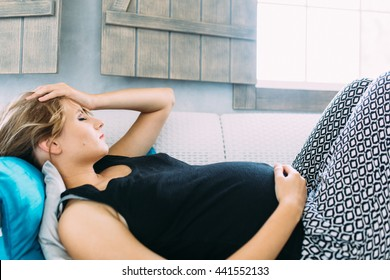 Young pregnant woman having a headache and she is lying on the sofa holding her belly and forehead
